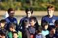 【日本代表PHOTO】子供たちと記念写真に納まる左から堂安、南野、大迫。写真:山崎 賢人(サッカーダイジェスト写真部)